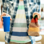 person holding a fast food package and glass with lunch in public