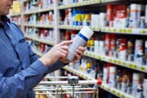 Adult man reading and analyzing labels on a can for sale in store.